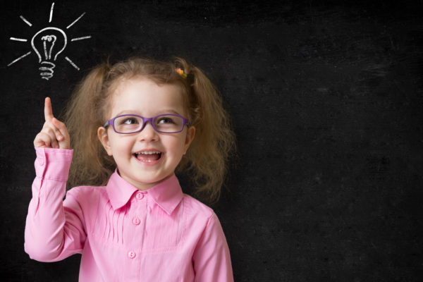 kid in glasses with idea lamp on school chalkboard in classroom
