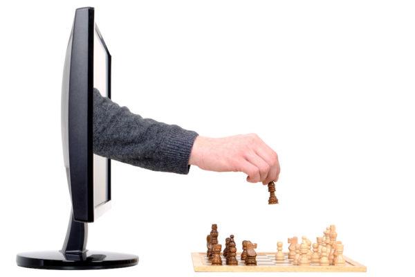 eine Hand kommend aus einem Computer spielt Schach
