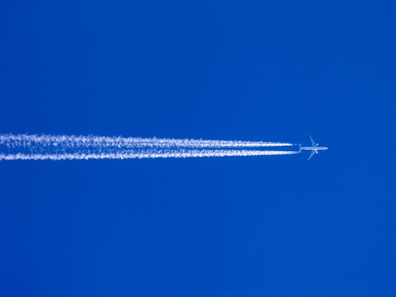 Ein Flugzeug mit Kondensstreifen vor blauem Himmel. Urlaubsreise und Luftverschmutzung