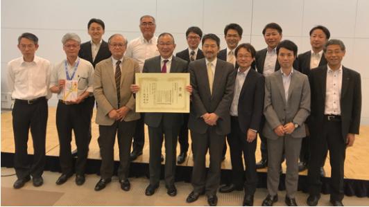 最優秀賞を受賞したWG 2M01の皆さんと西岡理事長、小川委員長