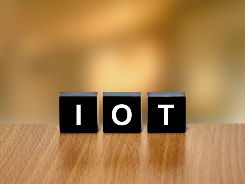 IOT or Internet of Things on black block with blurred background