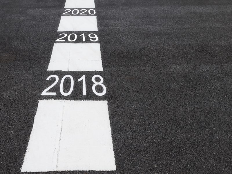 Number of 2018 to 2020 on asphalt road surface with marking lines, happy new year concept