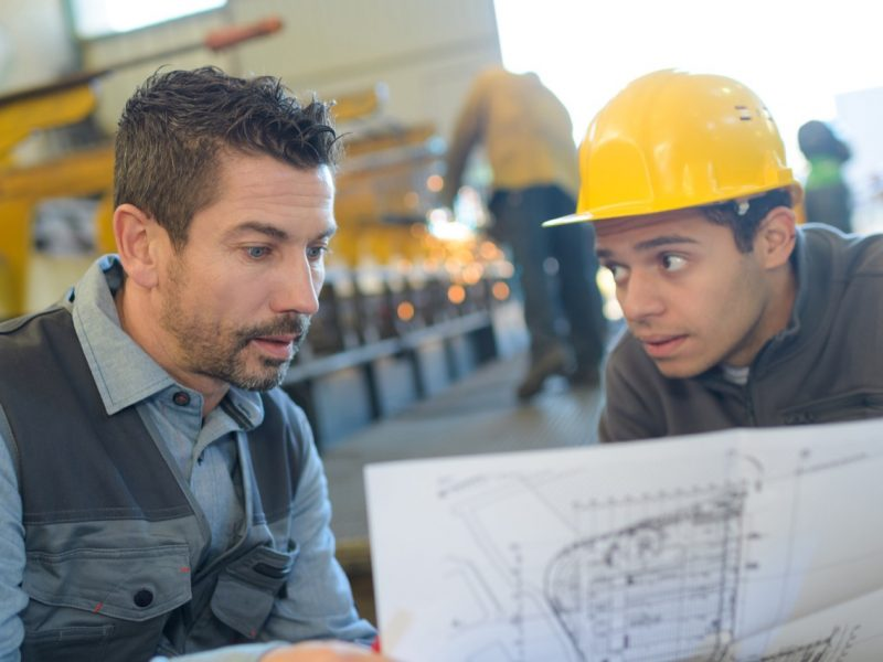 male supervisor with worker discussing over blueprints in industry