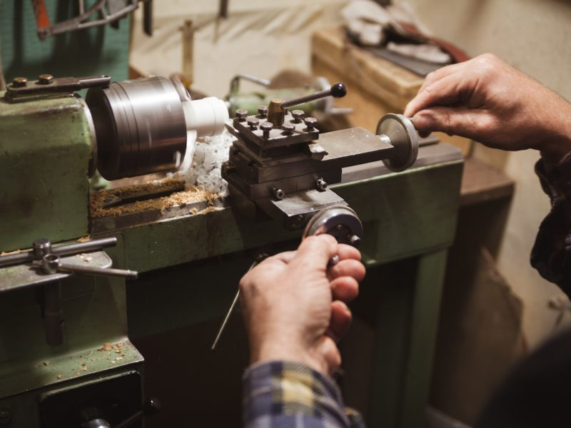 man's hands hold chisel near lathe