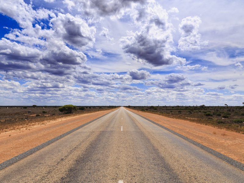 wide perspective view of tarmac road heading towards horizon under sunny summer sky between red soil roadsides with no vehicles around in nullarbor plain of South Australia