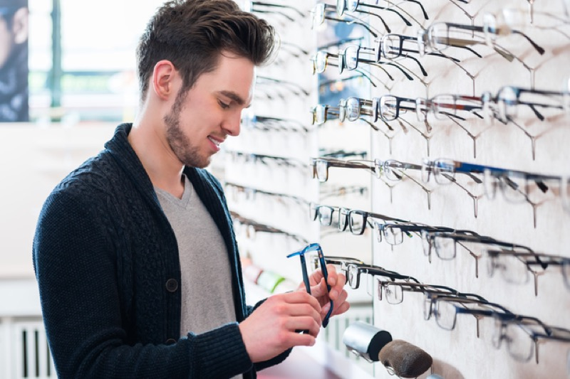 Man as customer choosing glasses from shelf in optician shop