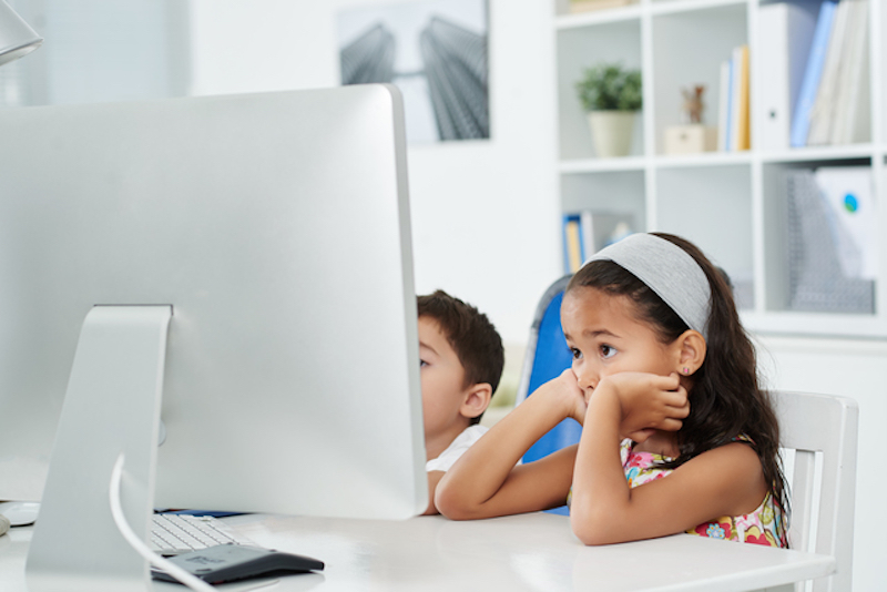 Two children sitting in front of computer in office
