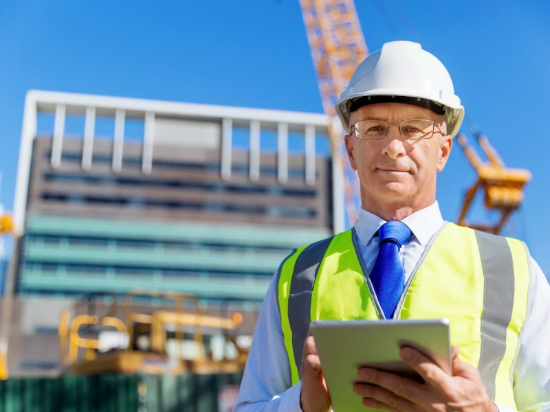 Engineer builder wearing safety vest with notepad at construction site