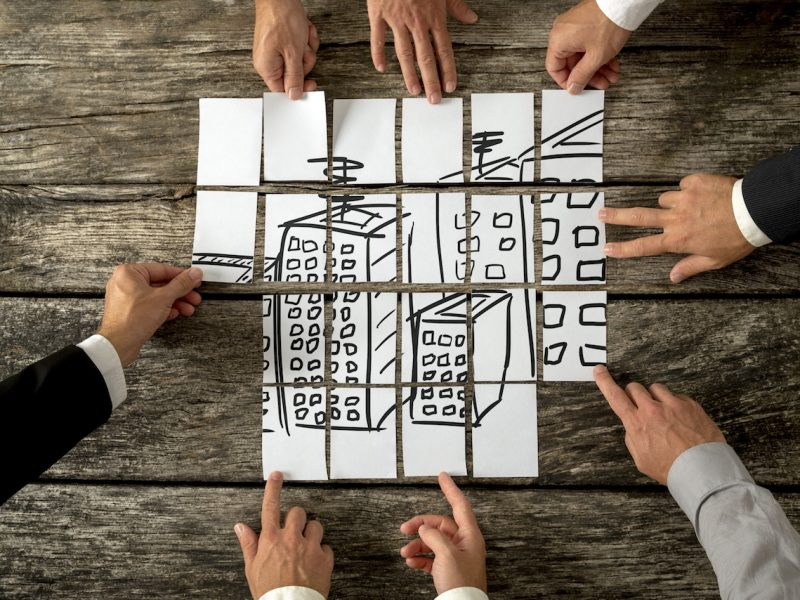 Top view of eight architects or urban planners cooperating in urban development and use of land by assembling hand drawn image of high buildings on white cards.