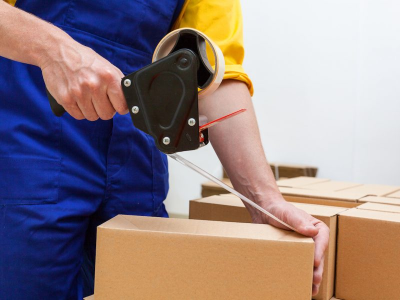 Closeup of a worker hands packing a box