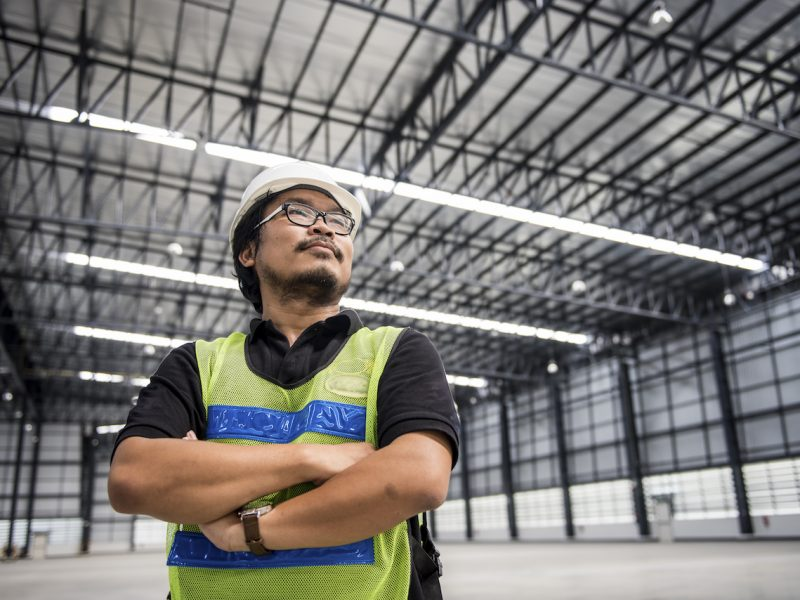 Engineer working and standing in new warehouse and space area