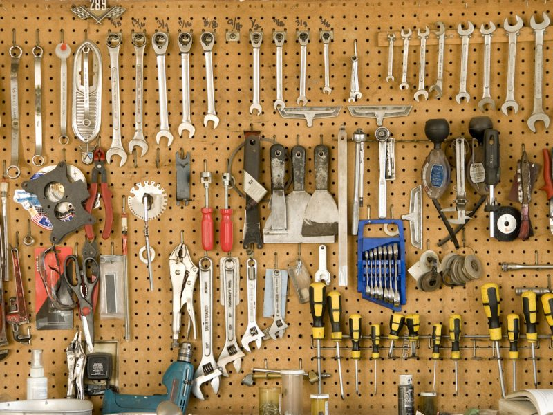 Many well-organized & well-used tools hang on a peg board in a garage.