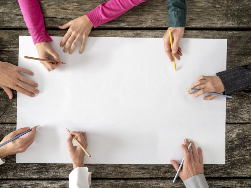 Teamwork and cooperation concept - top view of six people - men and women - drawing or writing on a large white blank sheet of paper.
