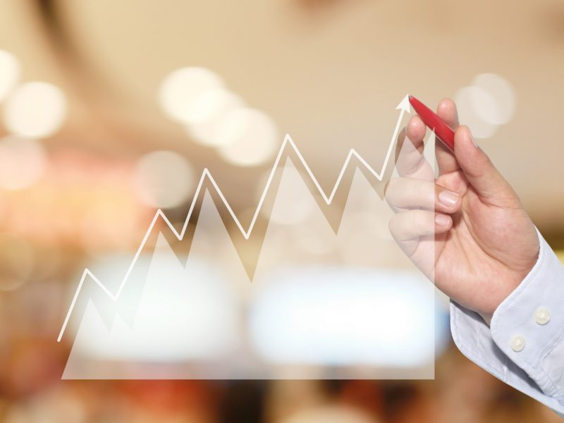 Businessman to point in peak of Business graph on abstract blur background,Concept financial symbols coming success and profitability.