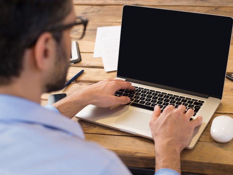 Back view of businessman sitting in front of laptop screen. Man typing on a modern laptop in an office. Young student typing on computer sitting at wooden table.