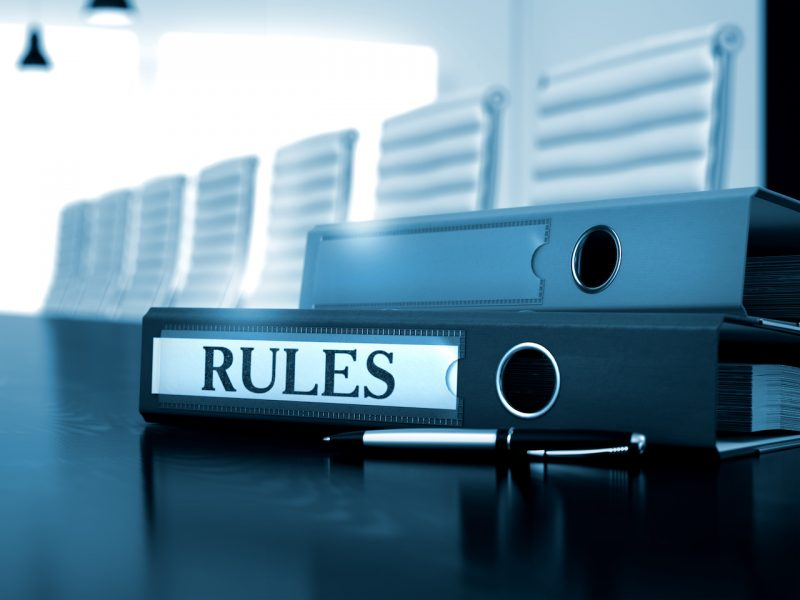 Rules - Folder on Black Wooden Desktop. Rules. Concept on Blurred Background. Rules - Illustration. Ring Binder with Inscription Rules on Office Desktop. 3D.