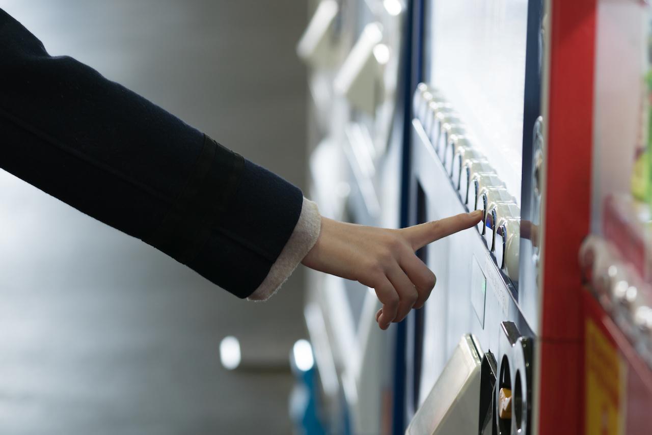 自動販売機で買う女性