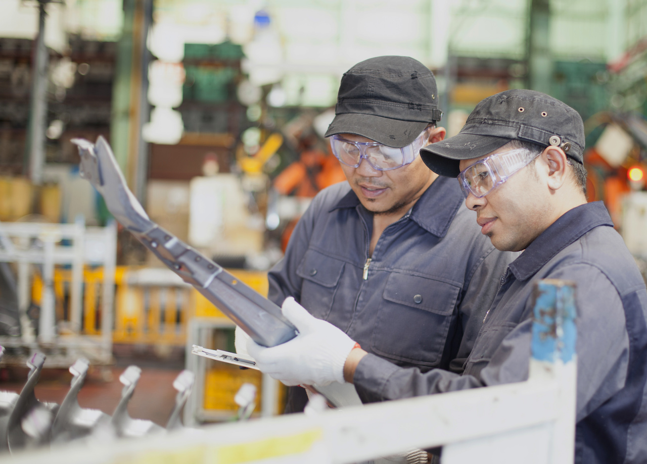 Two engineer checking metal production in workplace