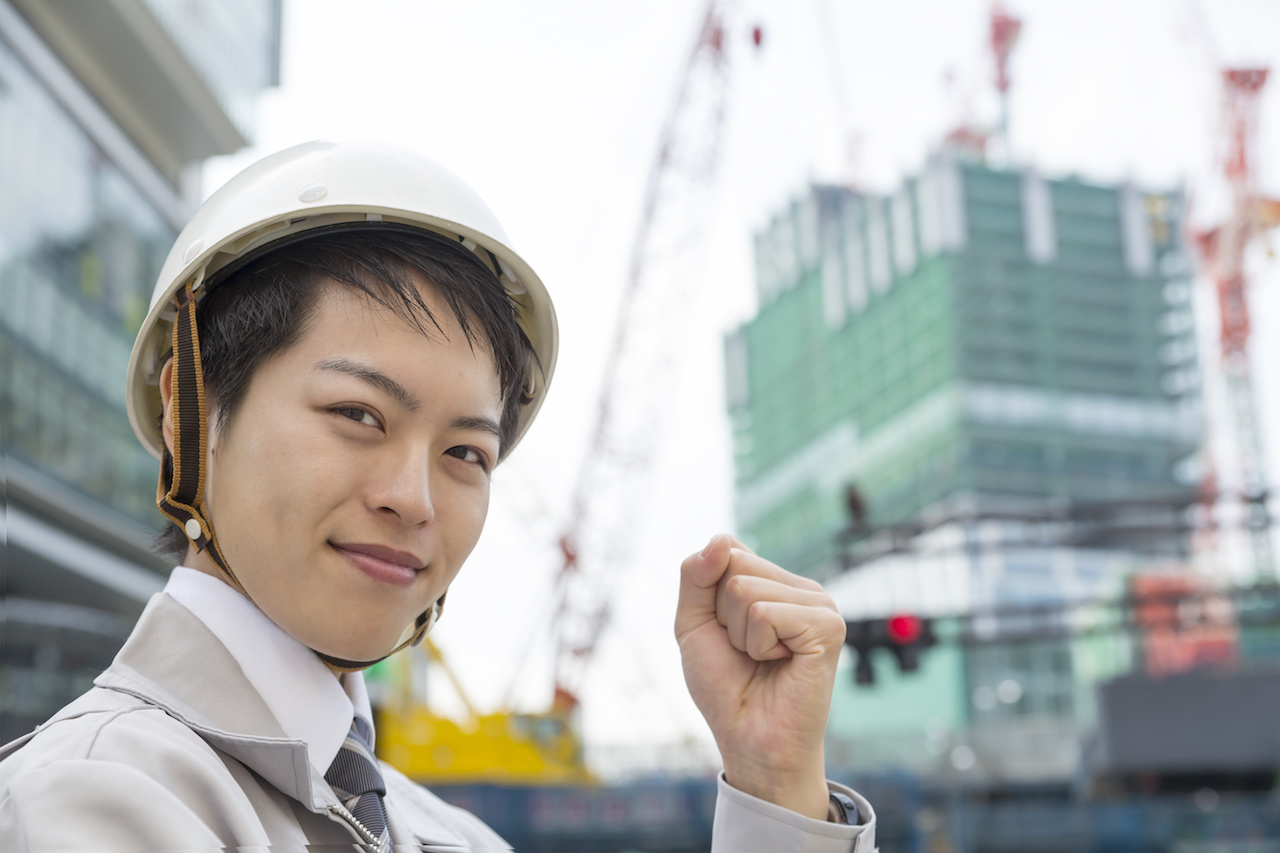 働く人イメージ ヘルメットと作業服のビジネスマン カメラ目線笑顔でガッツポーズ