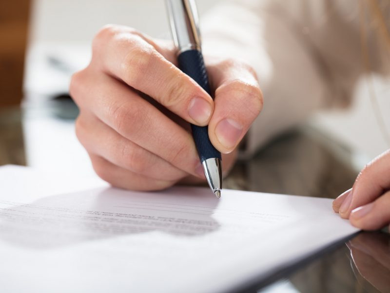 Close-up Of A Business Person Signing Document With Pen On The Desk