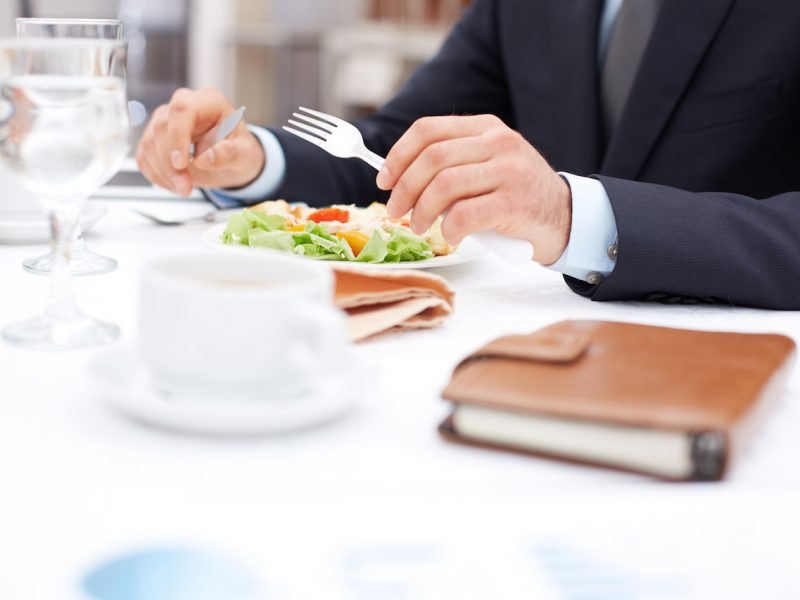Close-up of businessman hands holding knife and fork over vegetable salad during business lunch