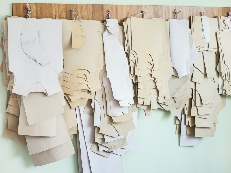 Many paper brown patterns for sewing clothes for babies and newborns of different sizes hanging on wall in sewing factory interior. Horizontal color photo.