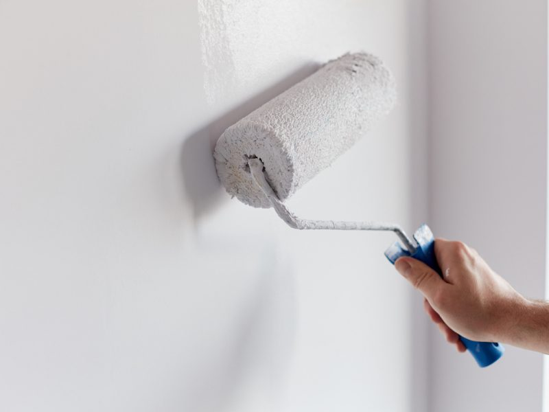 Male hand painting wall with paint roller. Painting apartment, renovating with white color paint