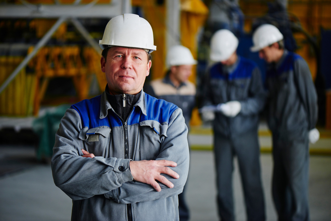 Portrait of a man in overalls and helmet on the background of a group of workers in factory building