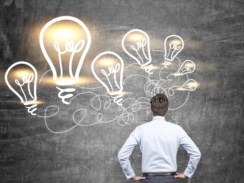Idea concept with businessman looking at illuminated lightbulb sketches on chalkboard background