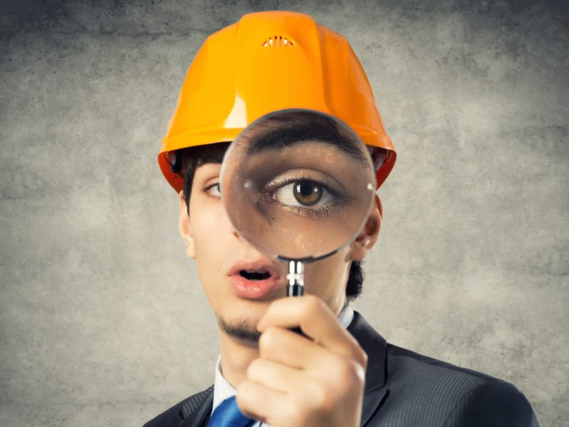 Portrait of engineer man in helmet looking through magnifying glass