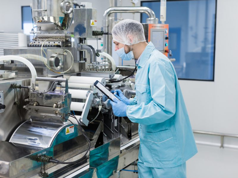 caucasian scientist in blue lab uniform configure manufacture machine with shafts and control panel, checking readings, making notes
