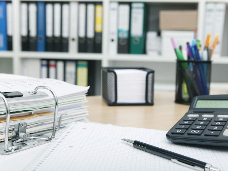 Schreibtisch in einem Büro mit Aktenordnern und Taschenrechner