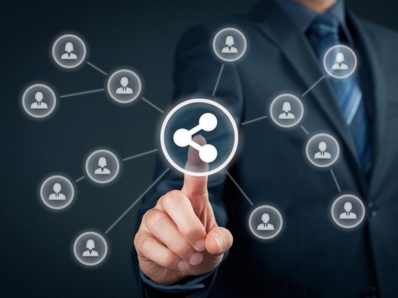Businessman click on share button connected with a network of business relationships.