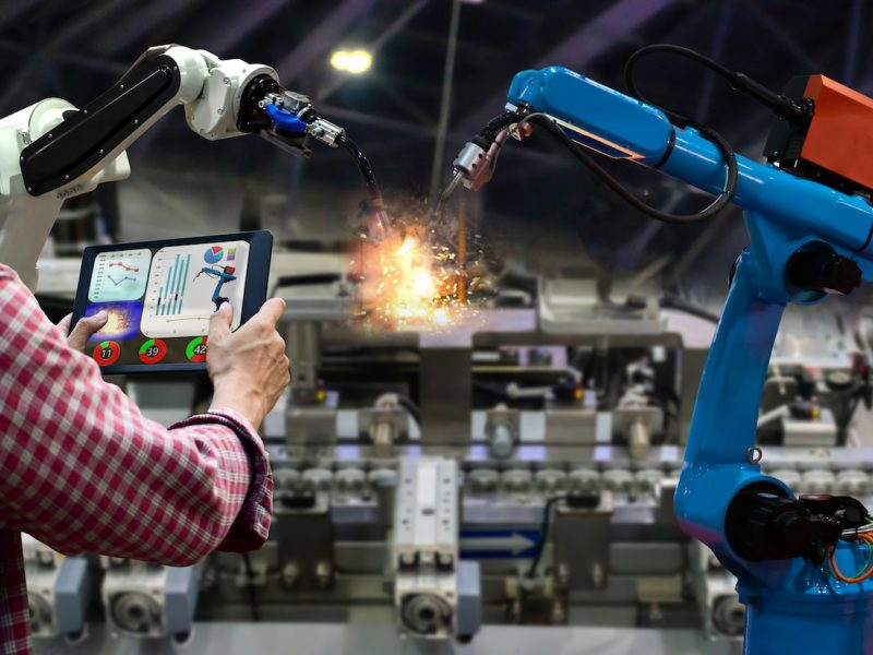 Engineer tablet control the production of factory parts manufacturing industry robots and mechanical arm