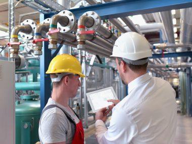 Teamwork in einer Industrieanlage - Arbeiter und Geschäftsmann vor Ort beim planen //