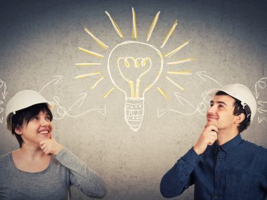 Ingenious construction engineers man and woman wearing protective helmet sharing thoughts together gathering ideas into a big lightbulb. Goal exchange, work partnership and teamwork innovation concept.