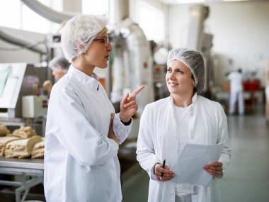 Two female workers discussing while standing in food factory. One of them holding paperwork and pen while other one speaking.