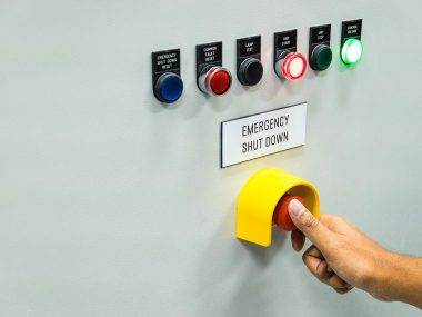 Technician is turning on emergency shutdown button on control pa