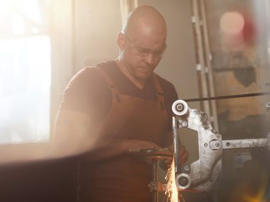 Serious concentrated bald worker in safety goggles and apron standing at rotary machine and grinding metal with sparkles