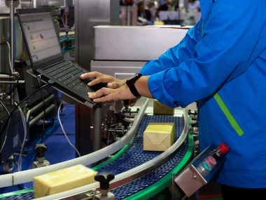 manufacturing engineer used computer to control product inspection system automation machine in modern factory while products are moving on the conveyor belt to warehouse for logistic transport. industrial and technology concept.