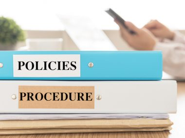 Policies and Procedures doucuments place on desk in meeting room.  Policy, Procedure concept.