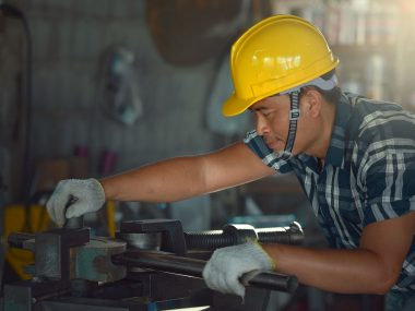 Young Asian worker in a metal cutting machine factory.