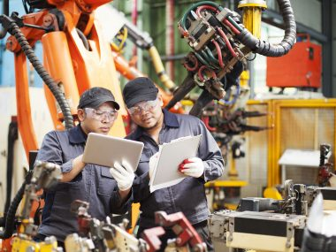 two employee checking production in tablet and notepad