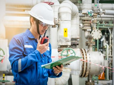 asian technician working with the walkie-talkie and checklist in industrial plant