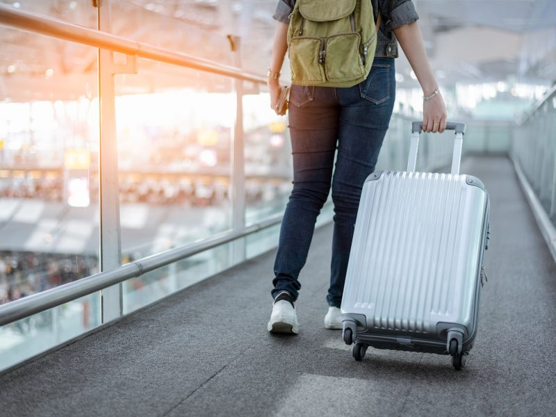 Close up lower body of woman traveler with luggage suitcase going to around the world by plane. Female tourist on automatic escalator in airport terminal.