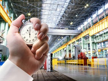 Machine shop of metallurgical works and stopwatch in male hand