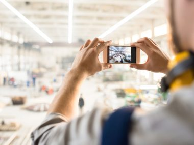 Over shoulder view of unrecognizable inspector wearing ear protectors standing at spacious production department of modern plant and taking picture on smartphone while carrying out inspection.