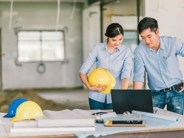 Young Asian engineers couple work together using notebook computer at building construction site. Civil engineering brainstorm meeting, architecture design, or house builder concept. With copy space
