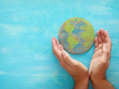 top view image of man hands holding earth globe over blue wooden background