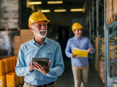 Picture of father and son walking through their warehouse with helmets on their heads. Father is holding digital tablet in his hand and looking at shelf full of boxes with smile on his face.